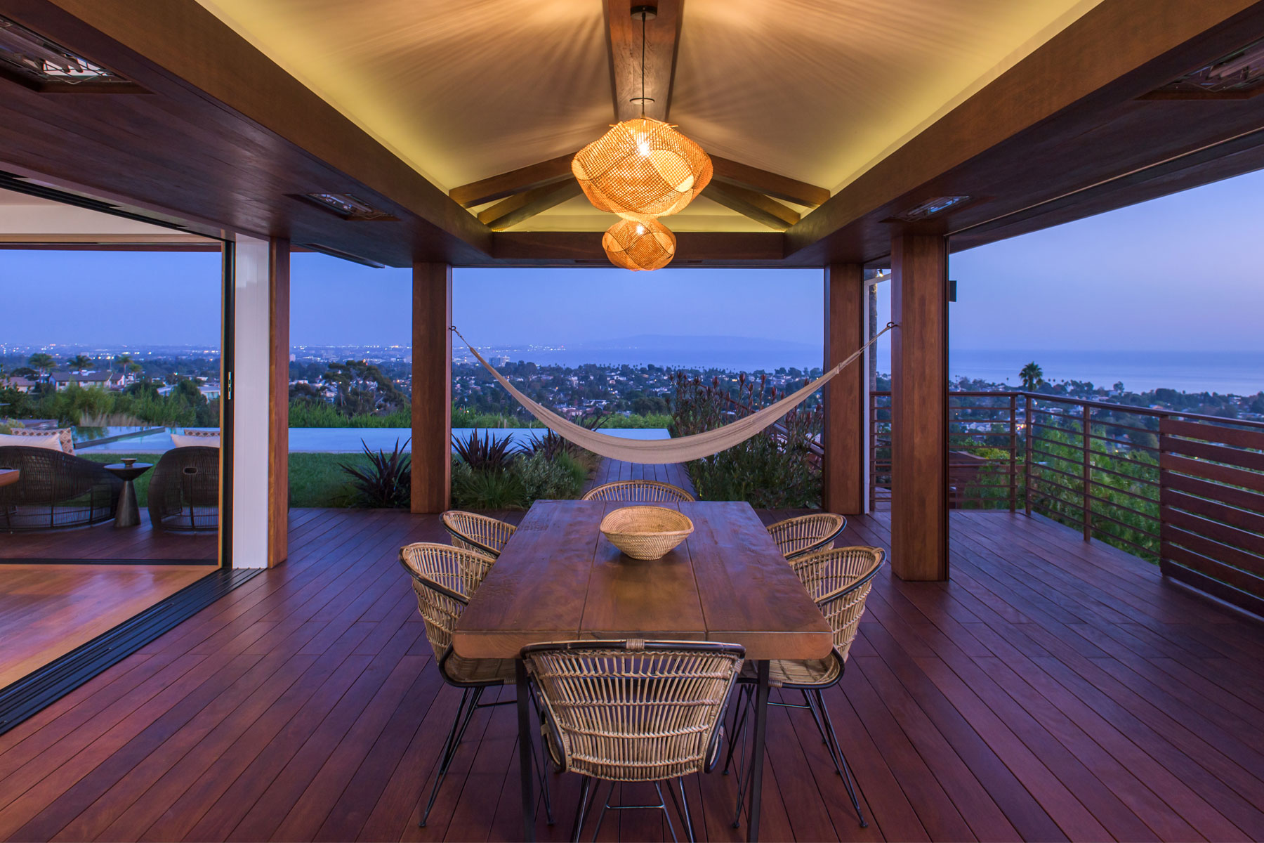 At night view of tranquil and elegant outdoor dining room wood deck and covered