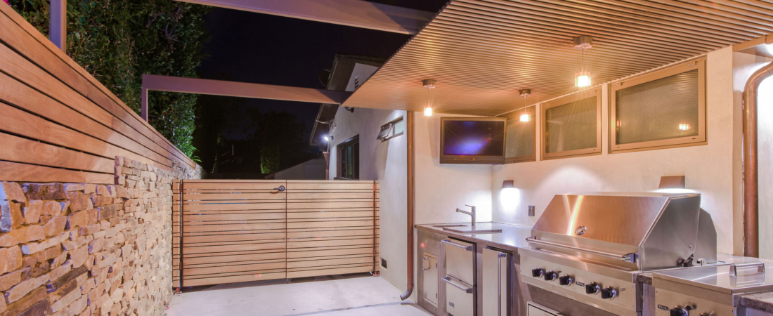 outdoor-kitchen-stone-wall-vertical-wood-slats-sunset-1100x450.jpg