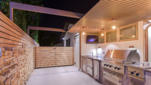 Outdoor kitchen stone wall vertical wood slats sunset